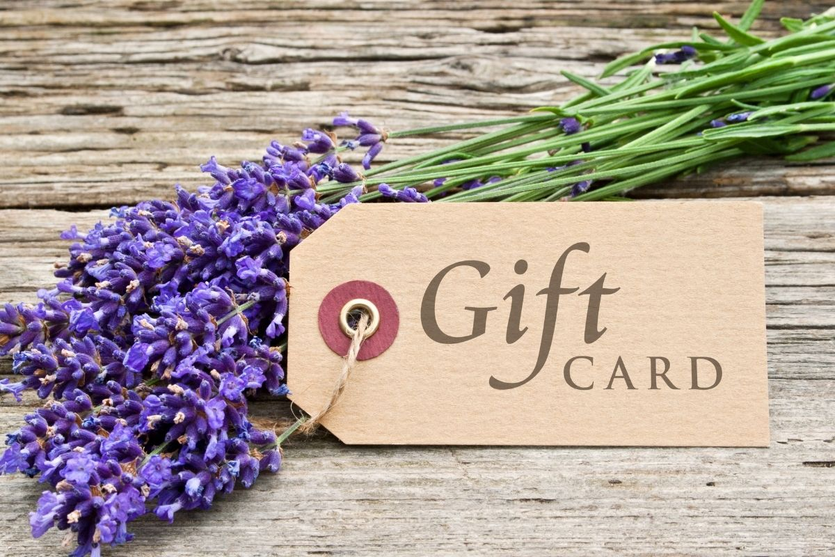 A gift card tag resting on a wood surface with purple flowers.